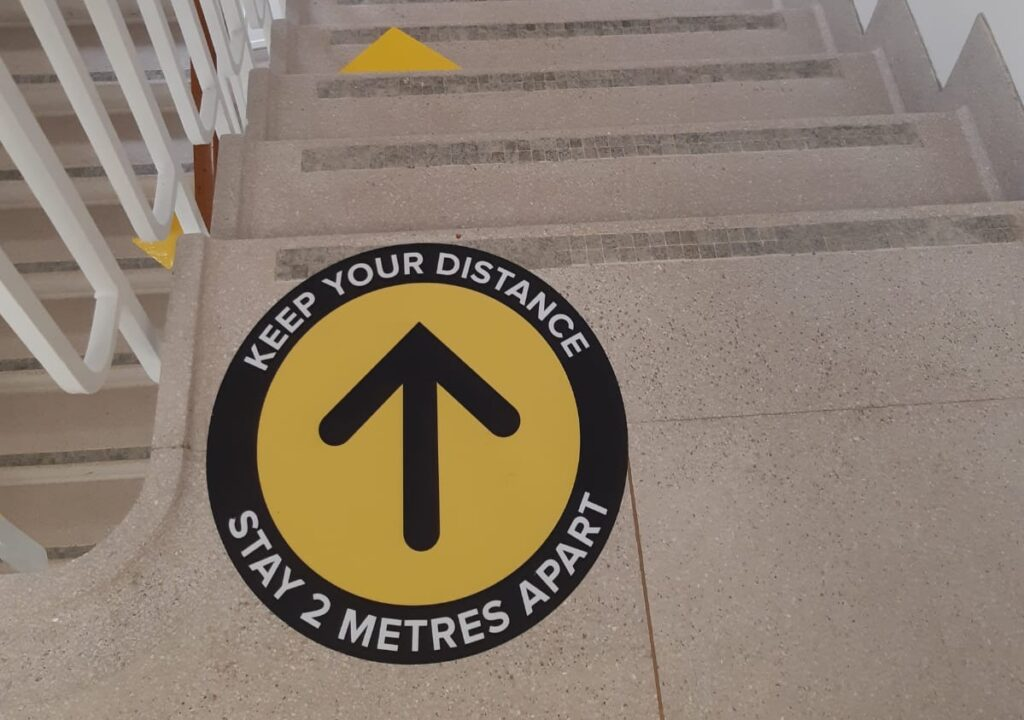 floor sign indicating people keep a 2 metre distance